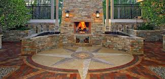 isokern outdoor fireplace with natural stone veneer exterior on brick paver patio with circular tile inlay
