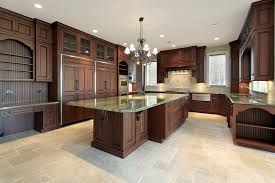 large custom kitchen with dark walnut wood cabinets and green granite countertops with large island