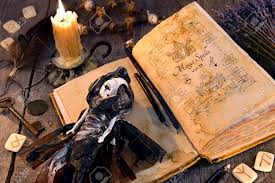 old book with black magic spells scary doll rune and burning candle on planks