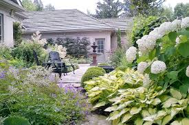 the front entry boasts of a symmetrical formal garden incorporating borders of clipped evergreens lavender hydrangeas and classic elements that help to