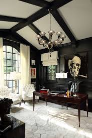 the mansion has a home office with black walls and white seating set in front of a fireplace grand chandelier brightens the room while glass windows lets