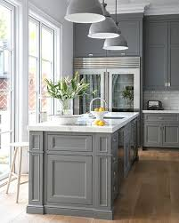 susan greenleaf grey kitchen features grey cabinets paired with white marble countertops and subway tile backsplash next to glass door refrigerator across