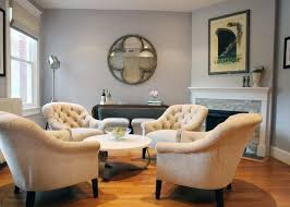 in this transitional living room a quartet of tufted armchairs stand in for a more traditional sofa and chairs grouping the light gray wall color