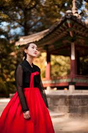 A Beautiful South Korean Girl Wearing A Traditional Red And Black Dress  Hanbok In A Royal