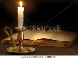 old book lit by the flame of a candle