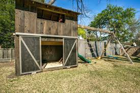swing set playhouses chic wooden in kids farmhouse with swing set next to building backyard playhouses alongside sandbox