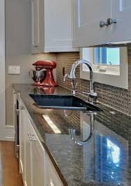 brown pearl granite counters polished to a highly refelective surface with a glass tile backsplash and
