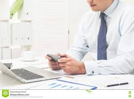 he is holding his smartphone with both hands and playing a game at his workplace in office concept of doing funny stuff at work