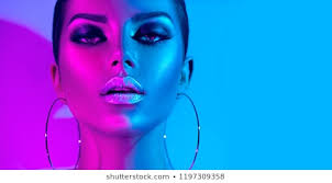 high fashion model metallic silver lips and face woman in colorful bright neon uv blue and