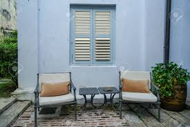 Outdoor garden furniture grey metal lounge chairs and side tables in front of blue building