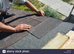 Roofer Installing Asphalt Shingles On House Construction