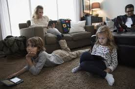 Family in living room on ipads and watching TV