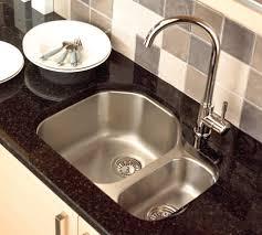 stainless steel undermount kitchen sink styles with white plates on black granite countertop under mosaic
