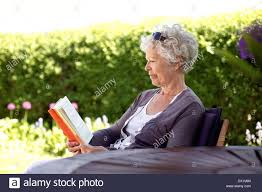 image of relaxed elder woman sitting in her backyard reading a book senior lady reading