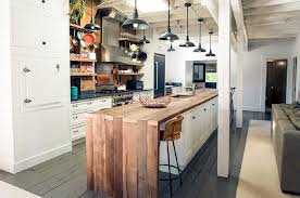narrow industrial kitchen white island with wooden countertop 8 black pendant lights gray painted wood flooring stainless steel backsplash regrigerator
