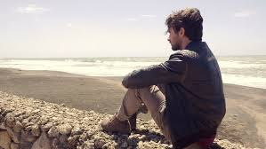 sad lonely man sitting in front of ocean thinking dolly shot 4k