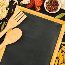 an overhead view of wooden spoon and spatula on blank slate with pasta ings free photo