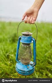 young girl holding a blue kerosene lamp stock photo