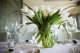 white table settings. A White Tablecloth With Simple Folded Napkins And Delicate Wine Goblets. At The Center Of Table Settings