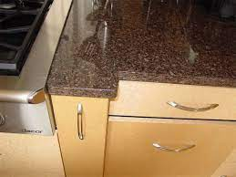 A quiet, understated stone, coffee brown granite has that soft, gentle brown that will make your kitchen as cozy as a steaming cup of coffee. Help Me Pick A Granite Natural Maple Cabinets Dark Floors Kitchen Countertops Countertops Natural Cabinets