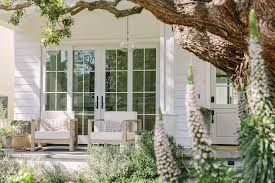 sliding doors framed by white siding and positioned behind restoration hardware aegean teak chairs placed on a concrete floor beneath hand blown glass