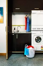 Compact small-space laundry: black cabinetry, black bifold doors, condenser  (non