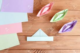 Set Of Origami Boats And Square Sheets Of Colored Paper On A