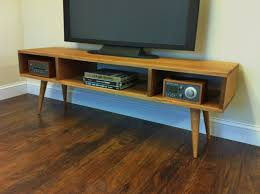 mid century modern inspired furniture. Brown Wooden Media Console With Three Racks And Four Legs On Floor Mid Century Modern Inspired Furniture