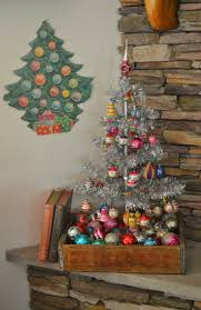 Small, silver tree in rustic, wood box filled with vintage Christmas balls.  The