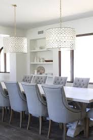 elegant transitional dining room boasts a light wood trestle dining table with gray tufted chairs under an oly studio serena drum chandelier