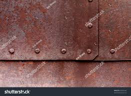 rivets in rusty metal. old flat metal with pitting, rust and rivets. rivets in rusty