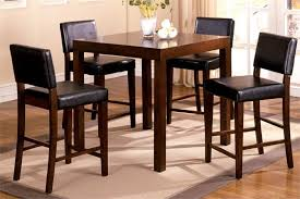 IKEA counter height table idea made of wooden with several wooden dining  chairs which have black