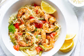 a bowl of shrimp scampi with angel hair pasta lemon asparagus and tomatoes