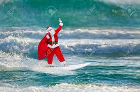 windsurfer with large holiday gifts sack go surfing with surfboard at ocean waves splashes