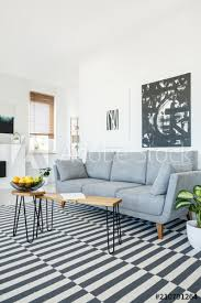real photo of a couch standing next to a wall with white and black paintings and