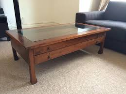 small spaces rustic living room design with old and vintage square mahogany coffee table with glass top and drawer on light brown carpet tiles ideas