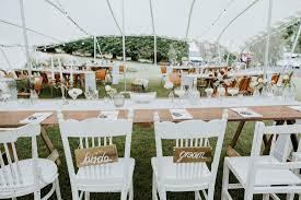 assorted white vintage chairs for bridal party teamed up with wooden trestle tables and wooden school chairs for guests