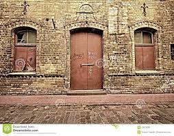old door and 2 windows in brick wall