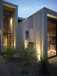 stunning house exterior with modern outdoor lighting and clear glass wall under flat roof