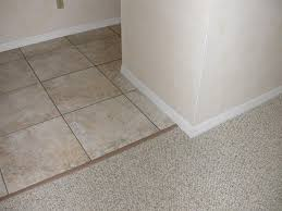 use a transition piece between tile and carpet to protect feet and install the base boards last so the carpet and tile is under them and not against them