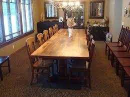 12 foot dining room table fits 12 to 14 people fortably it s a red oak on a iron adorned trestle base it has great seating all the way around