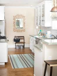 stripes fur rug on laminate kitchen flooring and glass door kitchen cabinet also small carve framed mirror above small wooden chair in minimalist kitchen