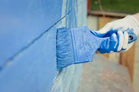 painting siding blue with paint brush