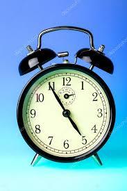 black old fashioned alarm clock on blue background photo by aksenovko