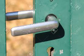 scratched door latch of a green garden gate stock photo 97809549
