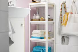 white bathroom cabinets. pink bathroom with a white sink and vesken shelving unit blue cabinets t