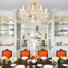 lavish transitional dining room with crystal chandelier orange dining chairs and glass china shelving