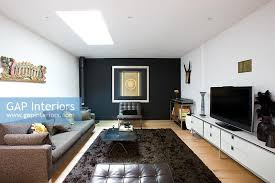 Contemporary living room with black feature wall and brown rug