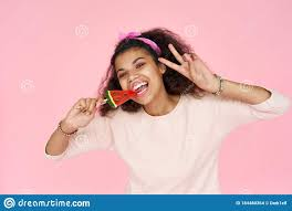 Smiling african gen z teen girl <b>bite candy</b> on <b>pink</b> studio background.