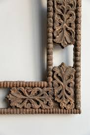 an intricately carved c20th anglo indian frame made from carefully cut fl motifs the wooden frame is ornately and elaborately openly carved